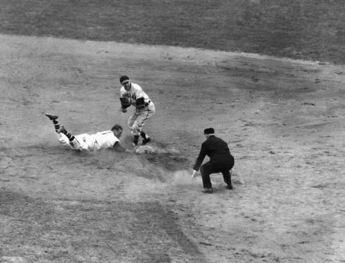 Boston Braves catcher Phil Masi slides safely back to second under Lou Boudreau, Cleveland shortstop, after being trapped off base by Cleveland pitcher Bob Feller in the eighth inning of the World Series opener in Boston's Braves Field on Oct. 6, 1948. Umpire Bill Steward calls the play. Masi scored on the next play when Tommy Holmes singled to left field, enabling the Braves to beat the Indians, 1-0. (AP Photo)